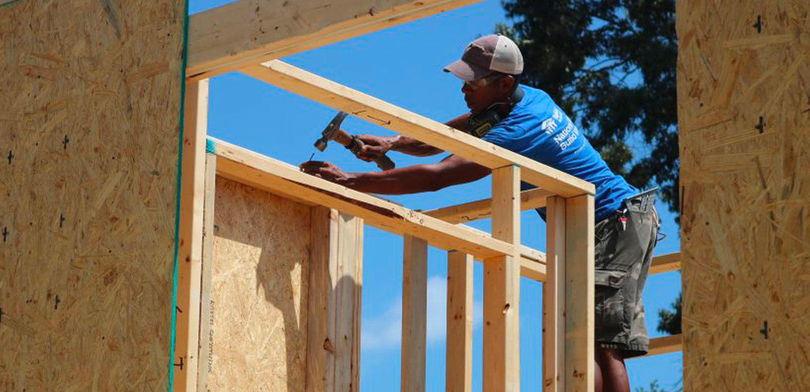 Man with hammer on house frame