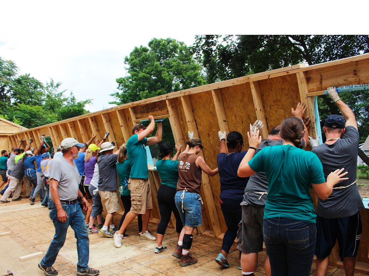 Habitat Team raising a side wall of a house